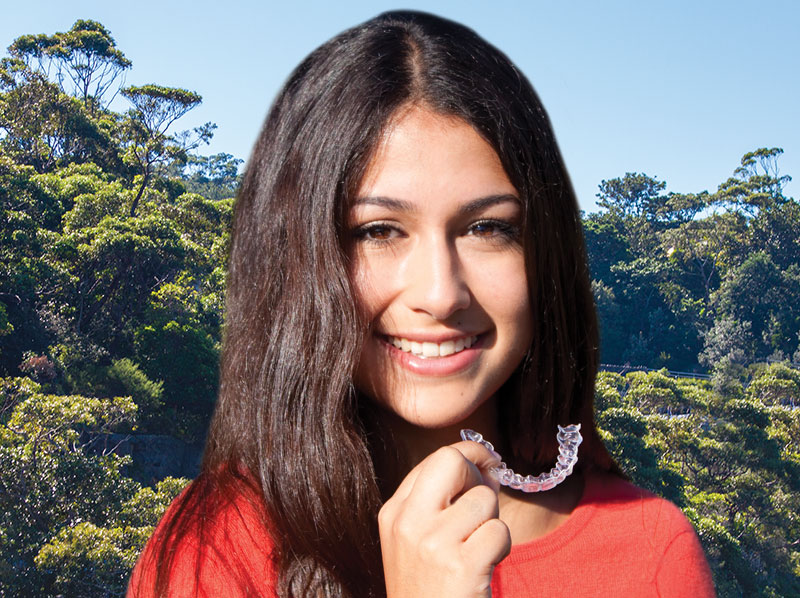 young-woman-smiling-holding-invisalign-braces